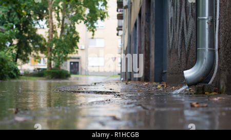 Downpipe is discharging water over a downpipe shoe straight into a flooded street. A few raindrops are hitting a surface of a puddle. Selective focus. - Stock Image