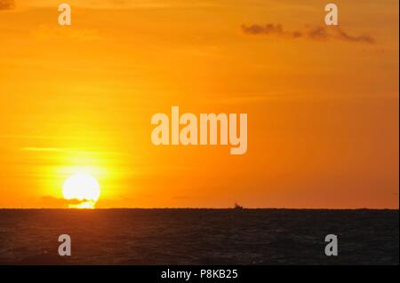 Colorful, partially cloudy orange sunset with silhouette charter fishing boat in distance speeding over the Atlantic Ocean as seen from Florida, USA. - Stock Image