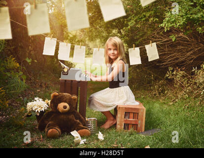 A creative school child is typing a story book on a typewriter with paper outside for an education, imagination - Stock Image