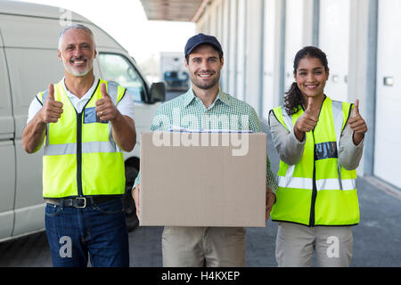 Portrait of warehouse worker and delivery man standing together - Stock Image