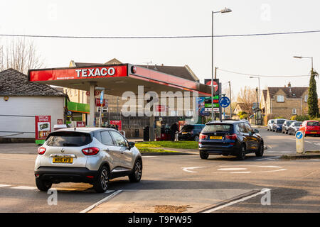 Cars driving past a Texaco fuel station with cars being filled in the late sunlight of a spring evening - Stock Image