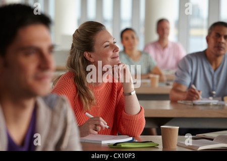 Mature students in class, woman with hand on chin - Stock Image