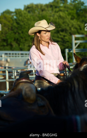 Tired Cowgirl riding horse after PRCA rodeo event in Bridgeport, Texas, USA - Stock Image