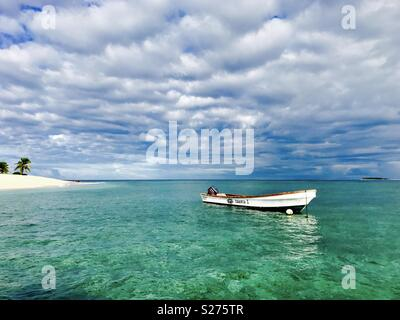 A boat anchored off Tavarua Island. Fiji. - Stock Image