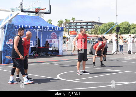 Coast Guard Lt. Cmdr Richard Mach assigned to Coast Guard Sector Los Angeles-Long Beach directs his fellow teammates on defensive strategies against Team Busciano during the 2018 Los Angeles Fleet Week 5-on-5 Basketball tournament in San Pedro, California, September 1st, 2018. Team Coast Guard 1 defeated Team Busciano 45-37 to advance to semifinals of the tournament. U.S. Coast Guard photo by Petty Officer 3rd Class DaVonte' Marrow. - Stock Image