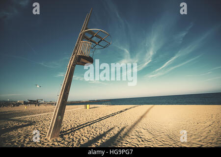 Wide angle shot of wooden lookout lifeguard tower at Barceloneta beach on sunny summer day with clear teal sky and - Stock Image