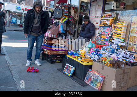 A street scene in Jackson Heights, Queens with a merchant and a young man looking a t a wind-up race car. - Stock Image
