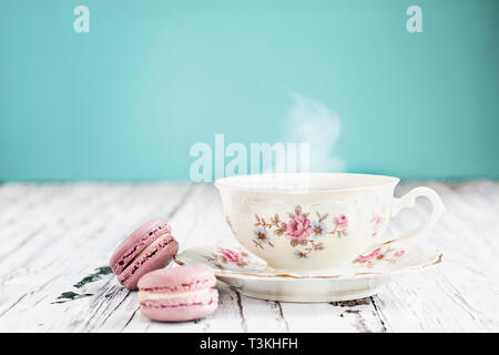 Antique Bavaria Winterling footed tea cup from the 1950s' with pink macarons on a rustic white table against a teal background.. - Stock Image