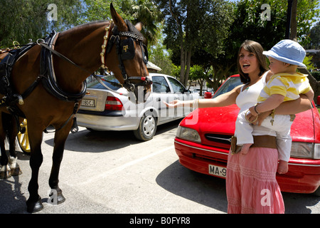 Mother holding toddler reaching out her hand to a stroke horse in the streets of in Mijas Pueblo, Costa del Sol, - Stock Image