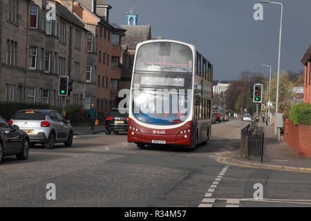 Traffic, including one of Lothian Buses double decker buses, in a suburb of Edinburgh - Stock Image