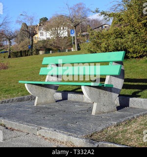 A green bench made of wood and concrete photographed on a sunny spring day in Nyon, Switzerland. In this photo you can also see some grass. - Stock Image