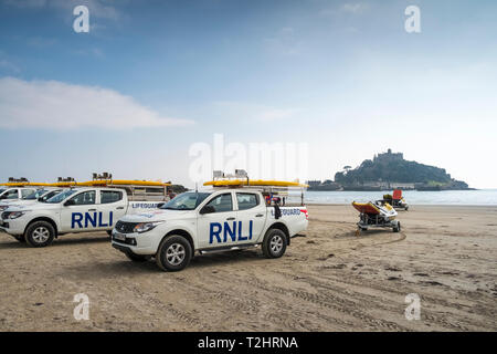 RNLI Lifeguards vehicles on beach at Marizion, Cornwall, England, UK, with St Michaels Mount in the background. - Stock Image