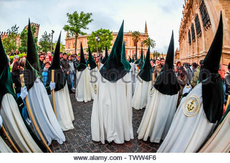 The procession of the Brotherhood (Hermandad) La Esperanza de Triana included hooded penitents (nazarenos) winds around the Seville Cathedral predawn - Stock Image