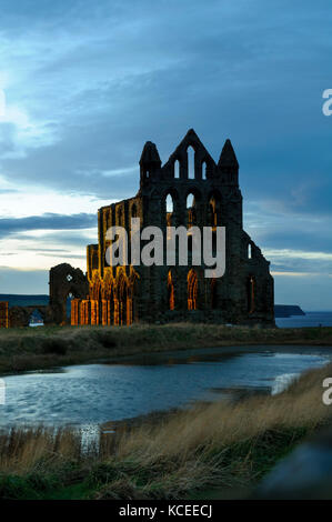 A view of the ruined abbey at twilight, just after the floodlights have come on, with a small pond in the foreground. - Stock Image
