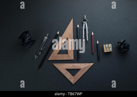 Drawing board flat lay with pencils, compasses, rulers and crumpled paper balls. The dark header for engineering, construction, and design with copy s - Stock Image