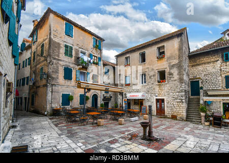 A small square in Old Town Kotor, Montenegro, with a water pump in the center surrounded by a cafe, market and apartments with colorful windows. - Stock Image