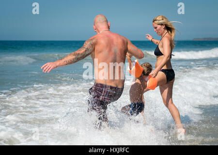 Family running into the ocean on the beach, Riviera Nayarit, Mexico - Stock Image