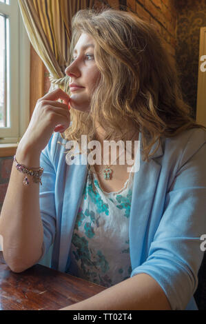 A beautiful, well dressed young woman, aged 23, with long wavy hair, sitting alone and looking pensively out of a window. - Stock Image