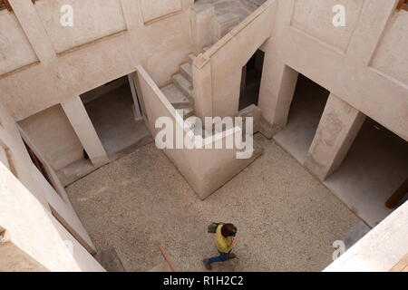 A woman walking in the courtyard of the Al Alawi House, located on the Pearl Trail, Muharraq, Kingdom of Bahrain - Stock Image