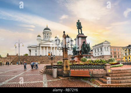 Tourists visiting the Senate Square,   Cathedral and monument statue of Czar Alexander II in the city center of Helsinki, Finland. - Stock Image