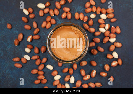 peanut butter in a glass jar on a blue concrete background. view from above - Stock Image