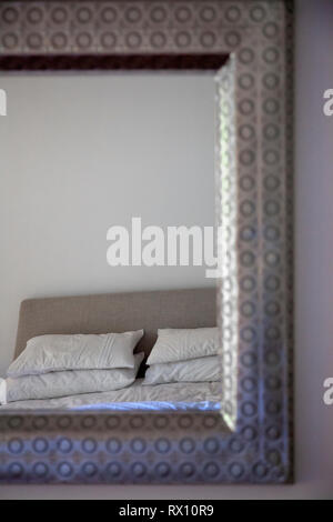 Bed Reflected in Mirror - Stock Image