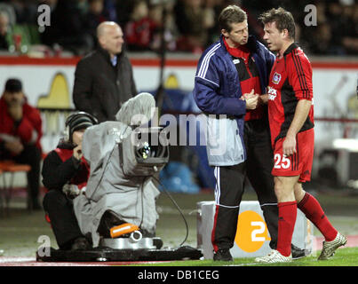 Bernd Schneider (R) of Leverkusen is cheered and substituted by his head coach Michael Skibbe (C) during the UEFA - Stock Image