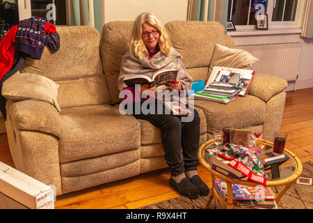 Older woman opening Christmas presents - Stock Image