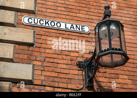 A street sign for Cuckoo Lane and an old-fashioned street lamp, in the historic city centre of Coventry in the UK. - Stock Image