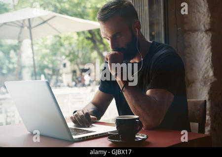 Concentrated Young Bearded Businessman Wearing Black Tshirt Working Laptop Urban Cafe.Man Sitting Wood Table Cup - Stock Image