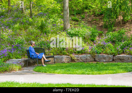 JONESBOROUGH, TN, USA-4/28/19: Attractive woman meditating on a bench in a beautiful park on a spring day. - Stock Image