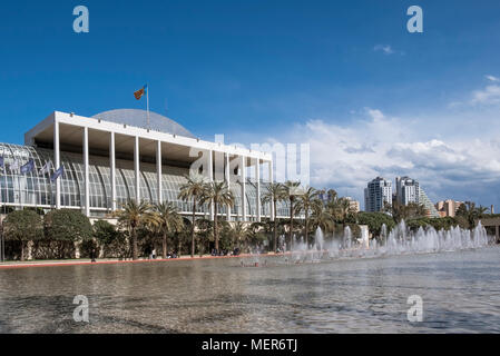 A water fountain in Jardines del Turia, a former riverbed running through Valencia, Spain, with the Palau De La Musica concert hall in the background. - Stock Image