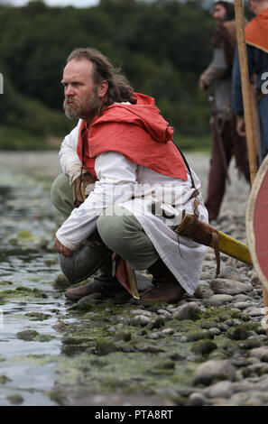 A Viking warrior takes a rest beside a river, part of a viking reenactment group which takes part in historical shows. - Stock Image
