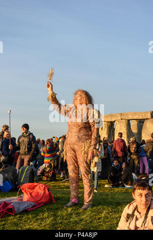 Stonehenge, Amesbury, UK, 21st  June 2018,   A woman in costume raising a sun symbol to the sky at the summer solstice  Credit: Estelle Bowden/Alamy Live News. - Stock Image