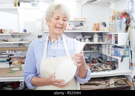 Senior Woman Holding Vase In Pottery Studio - Stock Image
