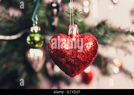 A decorative red heart hanging from a christmas tree - Stock Image