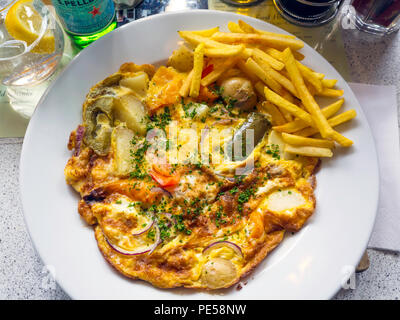 Lunchtime food a Spanish Omelette with a small portion of chipped potatoes - Stock Image