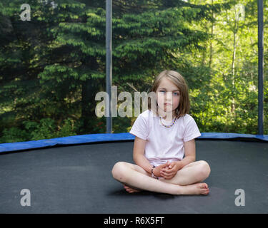 Young girl with neutral expression sitting with crossed legs on a trampoline looking at camera - Stock Image