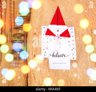 Christmas decoration on a wooden table with square gift box for celebration with snow falling and colorful bokeh - Stock Image