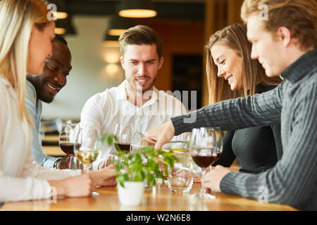 Young people having a glass of wine together in a bistro or restaurant - Stock Image
