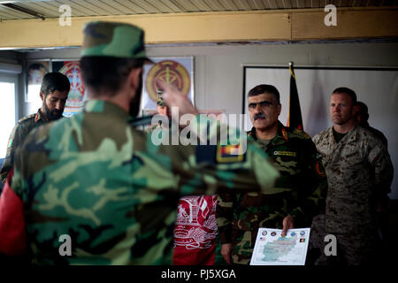 HELMAND PROVINCE, Afghanistan (August 26, 2018) – A soldier with the Afghan National Army (ANA) 215th Corps salutes Afghan Brig. Gen. Abdul Hadi, ANA 215th Corps deputy commander, during a graduation ceremony for a train-the-trainer course at the Regional Military Training Center on Camp Shorabak. The nearly month-long course taught instructors the basics of warrior training so they can, in turn, teach the upcoming classes of the new ANA Territorial Force who will assist in providing safe and secure elections to the people of Helmand and Nimroz provinces this October. (U.S. Marine Corps photo  - Stock Image