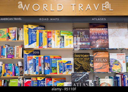 Cambridge, England - October 2018: Interior of a modern Waterstones bookshop, world travel section, with wooden shelves full of books. - Stock Image
