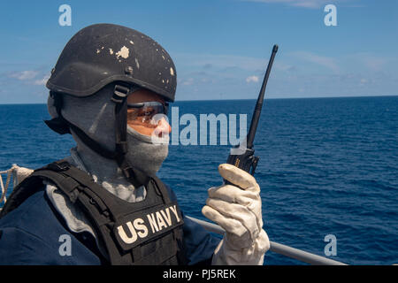 180826-N-AT530-0068 ATLANTIC OCEAN (Aug. 26, 2018) – Yeoman 3rd Class Shelby Warren scans the horizon as she mans an M2HB .50 caliber machine gun post on the amphibious dock landing ship USS Fort McHenry (LSD 43) during Carrier Strike Group FOUR (CSG 4) Amphibious Ready Group, Marine Expeditionary Unit exercise (ARGMEUEX). Kearsarge Amphibious Ready Group and 22nd Marine Expeditionary Unit are enhancing joint integration, lethality and collective capabilities of the Navy-Marine Corps team through joint planning and execution of challenging and realistic training scenarios. CSG-4 mentors, train - Stock Image