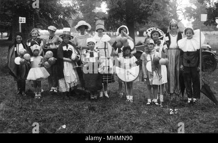 A group of children in fancy dress at a fete or carnival.  Among the costumes are a clown, a Welsh girl and a harem girl.       Date: c,1928 - Stock Image