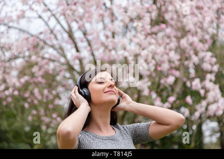 Young woman listening to music on wireless headphones in a park with cherry blossom trees. - Stock Image