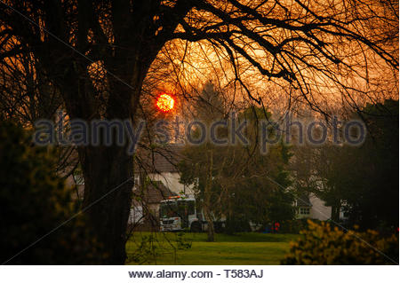 Sunrise the early morning sun peeks above the semi detached suburban houses & Liverpool Council refuse workers in Allerton, Liverpool L18 England UK - Stock Image