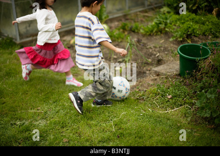 Boy aged six and sister five play soccer kicking ball into vegetable patch - Stock Image