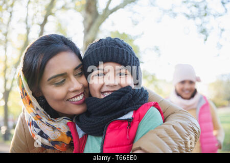 Portrait happy Muslim mother in hijab hugging son in autumn park - Stock Image