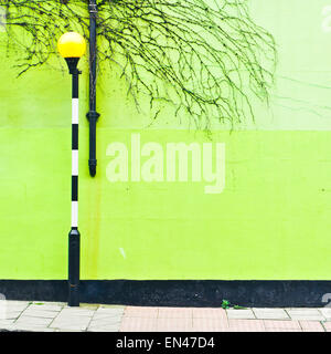 A light at a zebra crossing in front of a green wall in London, UK - Stock Image