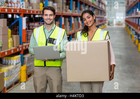 Portrait of warehouse workers standing with laptop and cardboard boxes - Stock Image